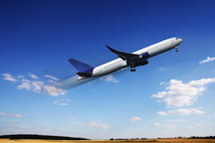 Airplane. Aircraft in flight over the blue clouds Royalty Free Stock Image
