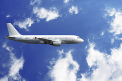 Airplane. White airplane in blue cloudy sky Stock Photography