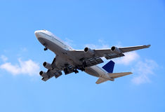 Airplane. Passenger airplane flying in bright blue sky Royalty Free Stock Image