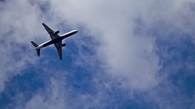 Airplane. Jet airplane shot from below against a blue sky with clouds flying to the top right of the picture Royalty Free Stock Photo