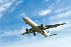 Airplane. Passenger airplane landing against blue cloudy sky Royalty Free Stock Image