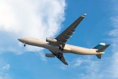 Airplane. Passenger airplane landing against blue cloudy sky Stock Photos