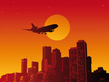 Airplane. Fly in the sunset in a town Royalty Free Stock Photos