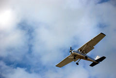 Airplane. Flying against a cloudy blue sky Stock Image