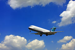 Airplane. An airplane which can be viewed as taking off or landing against a partly cloudy deep blue sky stock photo