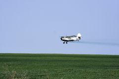 Airplane. Low flying crop duster  over field Royalty Free Stock Photography