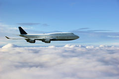 Airplane above the clouds. In front of blue sky stock images