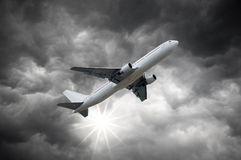 Airplane above Dark storm sky and shining Sun Royalty Free Stock Image