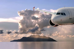 Airplane above the morning sea. Airplane is on the low altitude (landing). Sky, sea, island, clouds as the background .The picture is back lighted  by sunrise Royalty Free Stock Photography