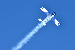 Airplane. In aerobatics with vapor trails Royalty Free Stock Image