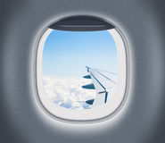 Airplane or aeroplane window with wing and cloudy sky behind. Air travel and flight concept Royalty Free Stock Photo