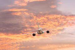 Airplane aft plane. In the sky at sunset sky Stock Photos