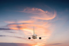 Airplane aft plane. In the sky at sunset sky Royalty Free Stock Photo