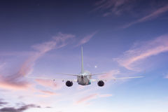 Airplane aft plane. In the sky at sunset sky Royalty Free Stock Photos