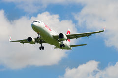 Airplane Airbus A320 HB-JLT company Swiss International Air Lines in a cloudy sky Stock Image