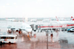 Airplane on the airfield. View through the airport terminal window. Blurred rainy background Royalty Free Stock Photo