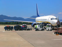 Airplane at airport. Loading baggage on airplane Royalty Free Stock Photography