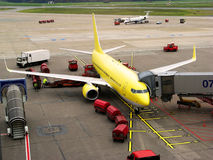Airplane at airport. A yellow Airplane at an airport and a jetway stock images
