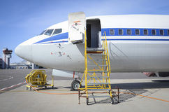 Airplane at the airport. Airplane parked on tarmac on sunny day with open doors Stock Images