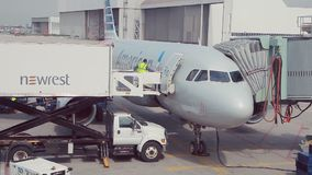Airplane at an airport with passenger gangway stock video footage