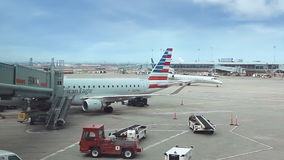Airplane at an airport with passenger gangway stock footage