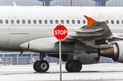 Airplane in airport portholes and wing, in front of them stop sign.  Royalty Free Stock Image