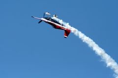 Airplane in airshow maneuvers. Airplane making a loop during airshow maneuvers Royalty Free Stock Photo