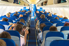 Airplane aisle with rear view of passengers Stock Photo