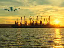 Airplane on the background of port cranes royalty free stock images