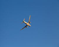Airplane Banking for a Turn against a blue sky Stock Image