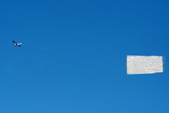 Airplane banner in blue sky. A small airplane tows an advertising banner across the clear blue sky. Banner is blank Royalty Free Stock Photo