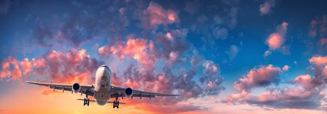 Airplane and beautiful sky. Landscape. With passenger airplane is flying in the blue sky with red, purple and orange clouds at sunrise. Travel. Passenger stock photos
