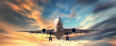 Airplane and beautiful sky with motion blur effect. Landscape with passenger airplane is flying in blurred blue sky with yellow clouds at sunset. Passenger royalty free stock photo