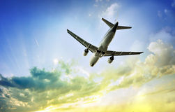 Airplane in the beautiful sunset sky Royalty Free Stock Photography