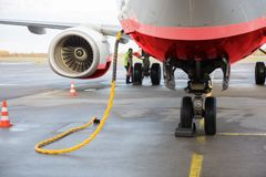 Airplane Being Charged While Worker Working On Runway. Commercial airplane being charged while worker working on wet runway royalty free stock photos