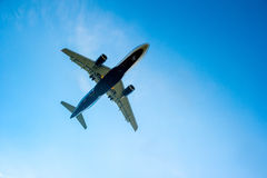 Airplane in the blue cloudless sky Stock Image