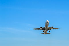 Airplane on the blue cloudy sky background. Bottom view Royalty Free Stock Photo