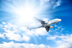 Airplane on blue sky and bright sun background Royalty Free Stock Photo