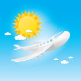 Airplane in blue sky with sun and clouds. Stock Images