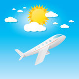 Airplane in blue sky with sun and clouds. Stock Photo