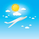 Airplane in blue sky with sun and clouds. Royalty Free Stock Image