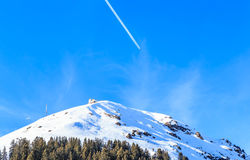 Airplane in a blue sky with traces. Mountain Hohe Salve. In winter. Ski resort Brixen im Thalef, Tyrol, Austria Stock Images