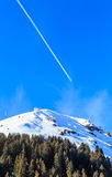 Airplane in a blue sky with traces. Mountain Hohe Salve. In winter. Ski resort Brixen im Thalef, Tyrol, Austria Royalty Free Stock Photography