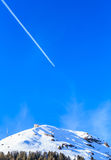 Airplane in a blue sky with traces. Mountain Hohe Salve. In winter. Ski resort Brixen im Thalef, Tyrol, Austria Royalty Free Stock Images