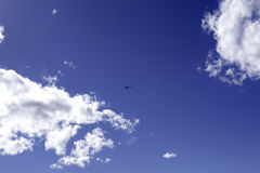 Airplane in the blue sky. Airplane in the blue sky, between two clouds. Space for text royalty free stock photo