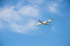 Airplane in blue sky. White airplane flying in blue sky with small clouds royalty free stock photo