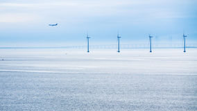 Airplane, bridge and offshore wind farm in morning Royalty Free Stock Photos