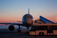 Airplane and bus on the early morning airport apron Stock Photography