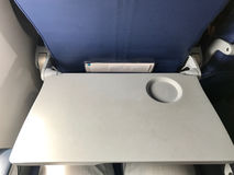 The grey Tray table for passenger in plane. Airplane cabin is all white. All its decorations are necessary stuffs and safety. The grey Tray table for passenger Stock Image