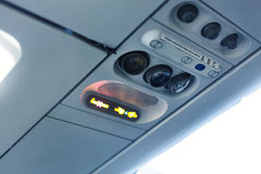 Airplane cabin interior detail. No smoking and seat belt signal Stock Photography